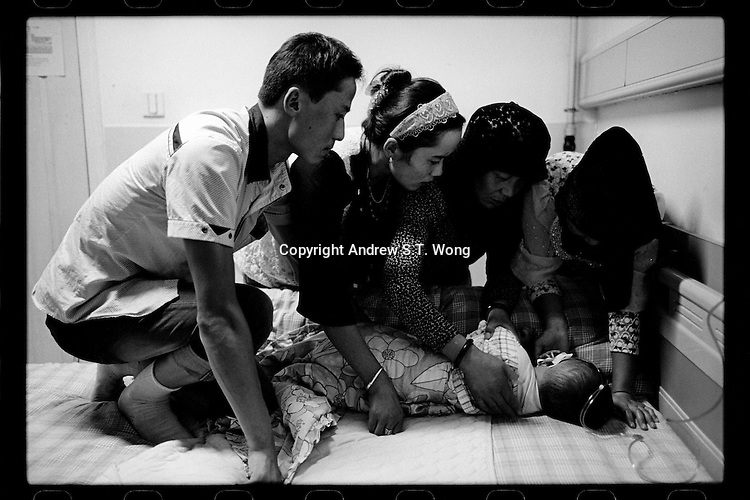 A Muslim couple and family members tend their son after a cleft lip operation organized by Smile Angel Foundation at a hospital in Xining, Qinghai province, China, August 2013. (Names withheld for privacy)