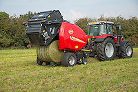 A Vicon round baler working in a field, Cheshire.