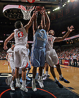 North Carolina forward Kennedy Meeks (3) goes up for the rebound with Virginia forward Anthony Gill (13) and Virginia guard Malcolm Brogdon (15) during an NCAA basketball game against Virginia Monday Jan. 20, 2014 in Charlottesville, VA. Virginia defeated North Carolina 76-61.