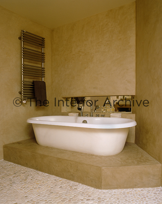 The free-standing contemporary bath tub has been placed on a raised concrete platform in this angular bathroom