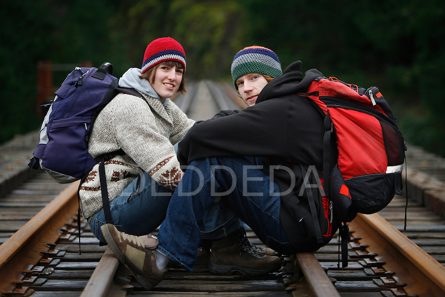 A young couple rests on a the E&N Railway while hiking in Goldstream Provincial Park near Victoria, British Columbia, BC, Canada.