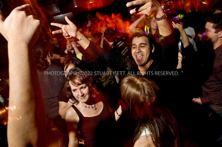 2/10/2006--Seattle, WA, USA..Ajay Dham (right, arms up in the arm) and Carla Jones (left, front) dance at a Bollywood party dance to Indian hits at the Baltic Room club in downtown Seattle. Manpreet Wadan of 'IHeartShiva.com' has organized the monthly events for over 4 years which typically draw in mixed crowds of Indians and non-Indians to enjoy a night of Bollywood/Bhangra music under a giant screen projection showing Bollywood movies...Photograph ©2007 Stuart Isett.All rights reserved
