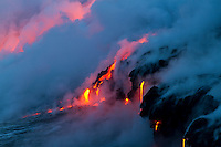 Lava flows into the ocean at dusk, creating new earth, purple smoke and a red glow at Hawai'i Volcanoes National Park and the Kalapana border, Big Island.