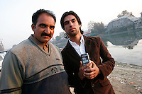 Modasir Ahmad Bhat (right) and his brother, a former militant, Manzoor Lone now seeks freedom through non violent politics. In his hands Modasir holds a mobile phone with photage apparently showing the shooting of unarmed protesters by Indian security forces. Srinagar, Kashmir, India. © Fredrik Naumann/Felix Features