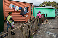 South Africa, Cape Town, Guguletu Township.  Two Houses, Women, Children.