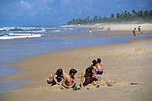 Sauipe, Bahia State, Brazil. Mother and pre-teen children digging in the sand on a glorious palm-fringed beach.