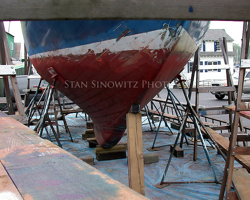 The wooden sailboat hauled out to have it's hull painted as seen between the horses.