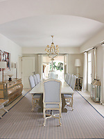 The long dining table seats ten with ease and has been placed on a modern rug running the entire length of the dining room