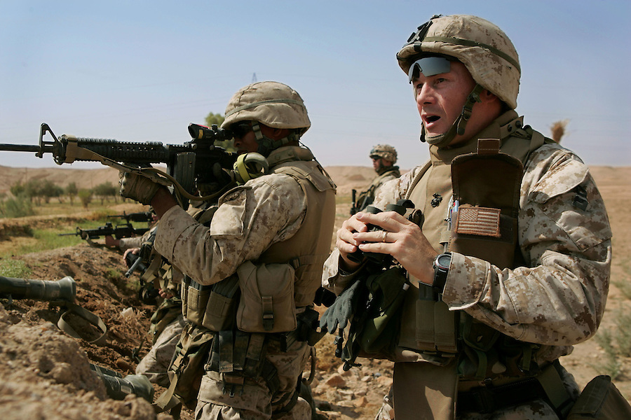 Following the detonation of an IED and an exchange of small arms fire, the Marines of H&S and India Companies 3rd Battalion 1st Marines (3/1) - including the battalion's commanding officer Lt. Col. J.R. Chessani (right) - surround and search a gas station on the outskirts of the al-Anbar Province city of Hit, Iraq on Sun. Sept. 18, 2005. A trio of men surrendered themselves after exiting the station under a white flag and were detained for questioning. The subsequent search of the gas station uncovered no insurgents or weapons.