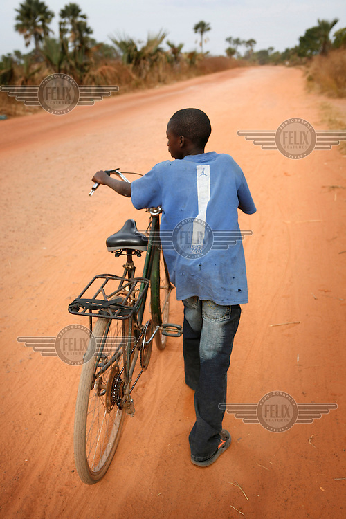 A boy walks with his bicycle towards his home village of Gunjur.