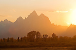The sun casts a warm glow over the Tetons and valley below as it sets behind the peaks at the end of an autumn day in Grand Teton National Park, Wyoming.