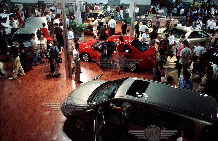 Potential buyers eye the newest offerings during a car show in Shanghai.