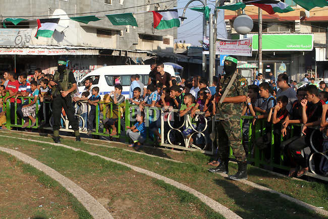 Palestinian children watch a military parade of members of the al-Qassam Brigades, the armed wing of the Hamas movement, to mark the first anniversary of the killing of Hamas's military commanders Mohammed Abu Shamala and Raed al-Attar, in Rafah in the southern Gaza Strip on August 21, 2015. Abu Shammala and al-Attar were killed by an Israeli air strike during the 50-day war between Israel and Hamas militants in the summer of 2014. Photo by Abed Rahim Khatib