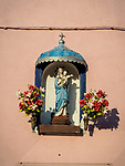 Madonna and flowers shrine on a wall. The colorful village of Burano, Italy.