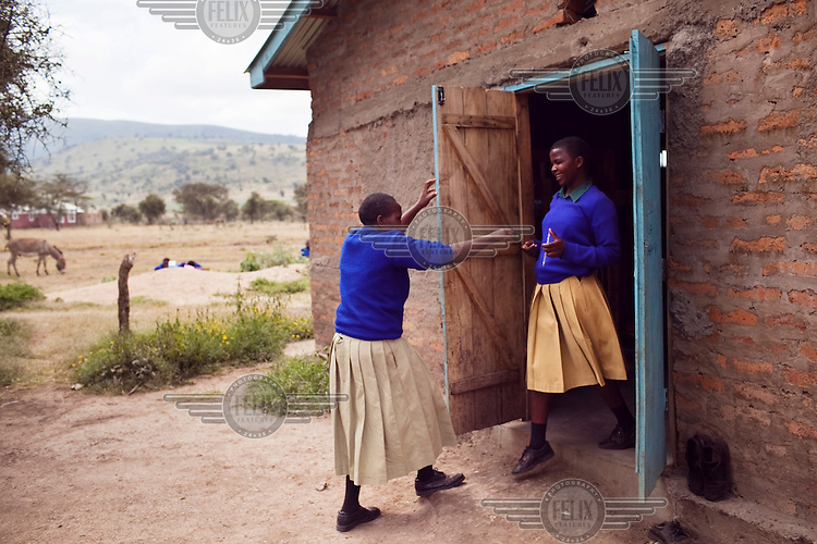 Survivors of FGM (female genital mutilation), from left, Naito Nagoto, 19, and Frida Alex, 18, chat outside the dormitory at the Noonkondin Secondary School run by Gemma Enolengila and Lesikar Olengila.