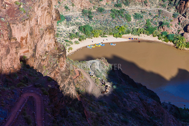Decending the steep trail to the colorado river near phantom ranch in the grand canyon. rafts and a mule train at the river