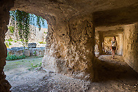 Eurialo Casle (Castello Eurialo), tourist exploring the tunnels at the Greek ruins near Syracuse (Siracusa), Sicily, Italy, Europe. This is a photo of Eurialo Casle (Castello Eurialo) showing a tourist exploring the tunnels at the Greek ruins near Syracuse (Siracusa), Sicily, Italy, Europe.