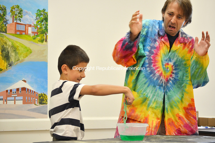 """WOLCOTT, CT- 23 July 2013 072213AP01- Jeton Selmani, 7, experiments with Jason Vance, a """"scienceteller"""", at the Wolcott Public Library. Children, ages 5 to 11, experimented with water, air, gas, and fire while following the story of Benjamin the bug in  """"The Tale of the Bugs of Blackwood.""""  Alexandra Pape. Republican-American"""