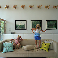 Twins, Sebastien and Adrienne, play on the sofa in the living room