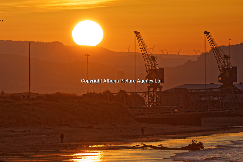 Two people walk on the beach as the sun rises over sand dunes and cranes in Swansea Bay, marking the start of another warm and sunny day in south Wales, UK. Wednesday 25 March 2020