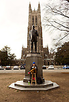 February 23, 2015. Durham, North Carolina.<br />  Robbie Florian, a senior in Visual and Media Studies, reads a Harry Potter book aloud at the foot of a statue of James Buchanan Duke, the son of Washington Duke, who founded Trinity College, which became Duke University.