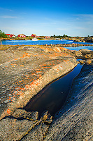 Klipphäll med faluröda fiskebodar i Stockholms  yttterskärgård