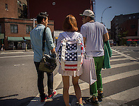 Japanese tourists, one wearing a Marc Jacobs backpack with an American flag design, in Greenwich Village in New York on Tuesday, August 27, 2013. (© Richard B. Levine)