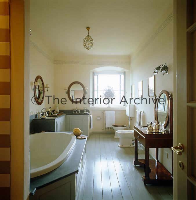 There is ample room for two wash basins, a large bath and an antique dressing table in this bright and sunny bathrooom