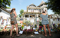 People lay flowers and notes during a memorial for Robin Williams (cq) at the home where the hit television show Mork and Mindy took place in Boulder, Colorado, Wednesday, August 13, 2014. Williams, who rose to fame starring in Mork and Mindy, died at the age of 63 from an apparent suicide. <br /> <br /> Photo by Matt Nager
