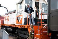 Railroad engineer starting the benefit train trip for the Osceola & St. Croix Valley Railway at the Minnesota Transportation Museum's Jackson Street Roundhouse. MP guard wearing World War II uniform.  St Paul Minnesota USA