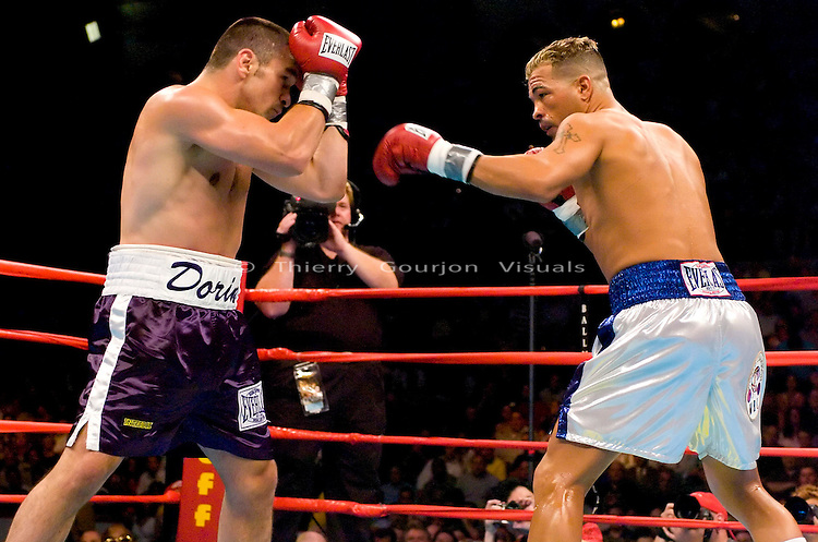 Arturo Gatti (right) connects against his opponent Leonard Dorin  during the WBC Super Lightweight Championship at the Boardwalk Hall in Atlantic City, New Jersey on July 24, 2004. Gatti won the fight by KO in the 2nd Round with a left body shot to the body. Photo by Thierry Gourjon.