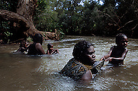 Women rangers swimming in Cadell River at Kolorbidahda  after a hunt and catching wild apples as they float down the river.