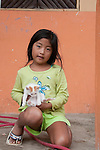 the little girl in puerto lopez ecuador was happy to show her little cat and have a photo taken