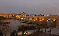 The Roman bridge in the evening, built 1st century BC over the Guadalquivir river, and in the distance, the Cathedral-Great Mosque of Cordoba, in Cordoba, Andalusia, Southern Spain. The first church built here by the Visigoths in the 7th century was split in half by the Moors, becoming half church, half mosque. In 784, the Great Mosque of Cordoba was built in its place, but in 1236 it was converted into a catholic church, with a Renaissance cathedral nave built in the 16th century. The historic centre of Cordoba is listed as a UNESCO World Heritage Site. Picture by Manuel Cohen