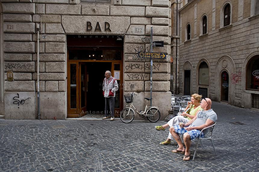Due turisti fanno colazione seduti in un vicolo nel centro storico di Roma. Tourists testing their cappuccino.