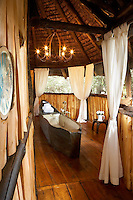 The bathroom of a boutique style luxurious wooden treehouse, made entirely of wood and grass. The interior has a rustic feel, with the talents of regional artists adding many of the finishing touches such as the wrought-iron chandelier made locally.  The bath is in the shape of a wooden carved canoe.