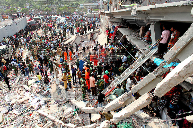 Rescue teams use ladders to access one of the floors of the collapsed Rana Plaza complex in search of survivors while onlookers wait. The 8 storey building, which housed a number of garment factories employing over 3,000 workers, collapsed on 24 April 2013. By 29 April, at least 380 were known to have died while hundreds remained missing. Workers who were worried about going to work in the building when they noticed cracks in the walls were told not to worry by the building's owner, Mohammed Sohel Rana, who is a member of the ruling Awami League's youth front. He fled his home and tried to escape to neighbouring India after the building collapsed but was caught by police and brought back to Dhaka. Some of the factories working in the Rana Plaza building produce cheap clothes for various European retailers including Primark in the UK and Mango, a Spanish label. . /Felix Features