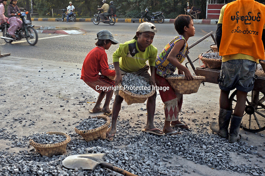 Children hump stones as they build a road on the outskirts of Mandalay, Burma November 08.  Child labour is a normal in Burma.<br /> <br /> Photo by Richard Jones