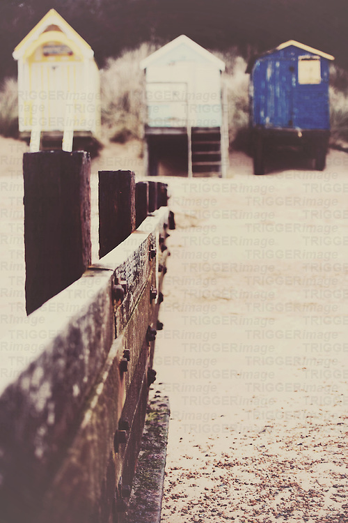 a low wood wall leading up to pretty retro beach huts at Wells-Next-The-Sea, England