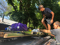 """READING INSPIRED RAFT<br />Edmond Niederman, 12, and his dad, Z (cq) Niederman, work on a raft Edmond and his brother, Clayton Niederman, 10, built with bamboo and empty plastic bottles they recycled into the raft's floatation. The boys got the idea for the project after reading """"The Raft,"""" a book about a child in Maine who paddled a raft, said their mom, Gina Niederman of Fayetteville. Brisk sales of kayaks made it difficult for the family to find kayaks to buy and that also helped spark the project.<br />(Courtesy photo)"""