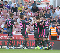Leeds United's Stuart Dallas is swamped by team-mates as he celebrates scoring the opening goal<br /> <br /> Photographer Stephen White/CameraSport<br /> <br /> The Premier League - Stoke City v Leeds United - Saturday August 24th 2019 - bet365 Stadium - Stoke-on-Trent<br /> <br /> World Copyright © 2019 CameraSport. All rights reserved. 43 Linden Ave. Countesthorpe. Leicester. England. LE8 5PG - Tel: +44 (0) 116 277 4147 - admin@camerasport.com - www.camerasport.com