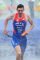 09 JUL 2011 - PARIS, FRA - A competitor runs under the showers after finishing the swim during the men's French Grand Prix series race (PHOTO (C) NIGEL FARROW)