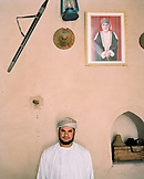 OMAN, man in traditional clothing standing by wall