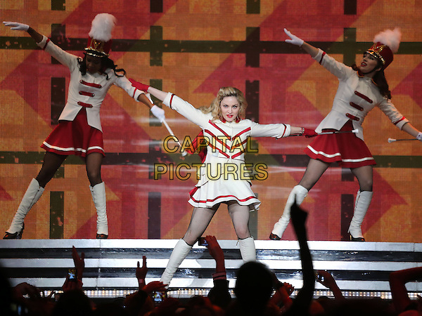 Madonna (Madonna Louise Ciccone) .Madonna performs at The Grand Garden Arena inside the MGM Grand Hotel and Casino, Las Vegas, Nevada, USA, .13th October 2012..music concert gig show live on stage performing full length red white cheerleader outfit costume knee high  boots baton arms outstretched collar gloves dancing .CAP/ADM/MJT.© MJT/AdMedia/Capital Pictures.