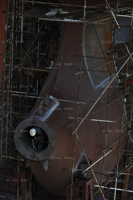 A shipyard worker operates in the propeller housing of a ship that is under construction at the Dalian shipyard in Dalian, Liaonin Province, China on 23 April 2011. China's shipping industry is expected to make a strong recovery as over capacity is smaller than expected and China's demand for raw materials needs more ships to transport them.