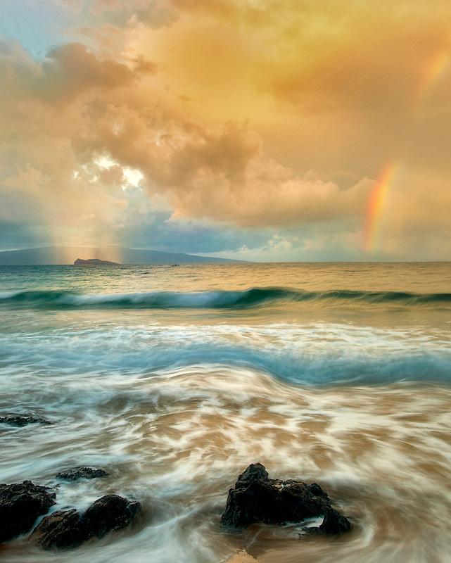 Maui coast with waves and rainbow with lighgt and rain on Molokini. Hawaii