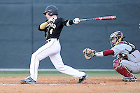 Catcher Carson Wain (4) of the Wofford College Terriers bats in a game against the Boston College Eagles on Friday, February 13, 2015, at Russell C. King Field in Spartanburg, South Carolina. The BC catcher is Nick Sciortino. Wofford won, 8-4. (Tom Priddy/Four Seam Images)