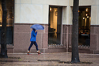 Woman holding an umbrella walks down the side walk in downtown Austin, Texas on a gray rainy day - Stock Image.