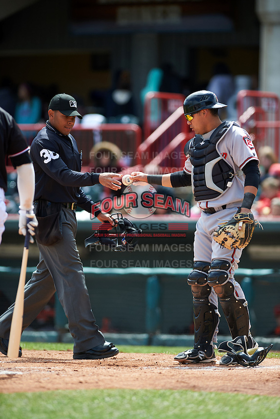 Umpire Jeremie Rehak takes a ball from Richmond Flying Squirrels catcher Eliezer Zambrano (2) during a game against the Erie Seawolves on May 20, 2015 at Jerry Uht Park in Erie, Pennsylvania.  Erie defeated Richmond 5-2.  (Mike Janes/Four Seam Images)