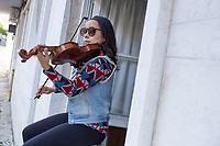LISBON, PORTUGAL - April 12: A violinist plays for her neighbors from her window, to cheer up the quarantine on April 12, 2020 in Lisbon, Portugal. <br /> The covid-19 pandemic has spread at breakneck speed, and quarantining more than 3.9 billion people, closed in their homes - more than half of the planet's population.<br /> Photo by Luis Boza/VIEWpress vía Getty Images